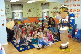 Fire prevention coordinator and fightfigher/EMT Lisa Glass shows the class at Helping Hearts Day Care what full gear looks like