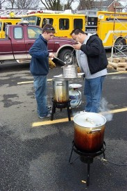 Firefighters Mike Predmore and Bill Wohl, Jr. check the turkey cookers at the annual Xmas lunch