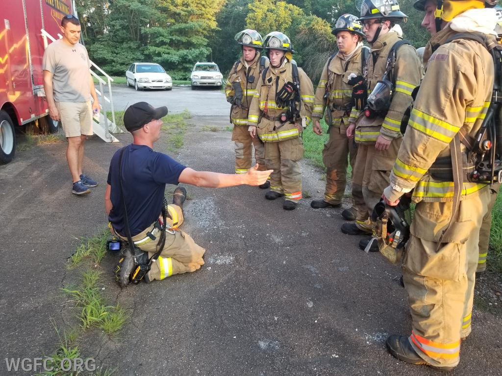 "2nd Lieutenant Matt Glass demonstrating how far a firefighter can ""sweep"" with one hand, and even further into a room with an outstretched tool."