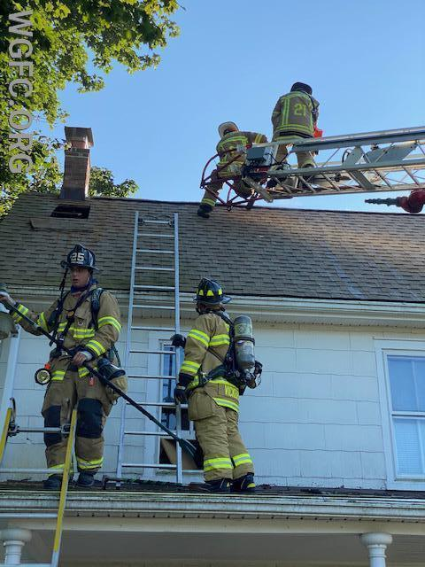 Here crews from Oxford and Longwood work on ventilation, relieving heat and smoke from the attic fire location.