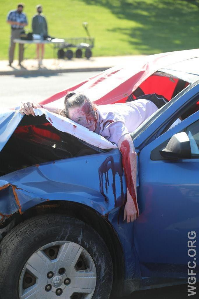 A student volunteer with realistic make up was used to simulate a seriously injured driver who was partially ejected from the car -- these realistic images deliver a stark yet important message to student drivers.