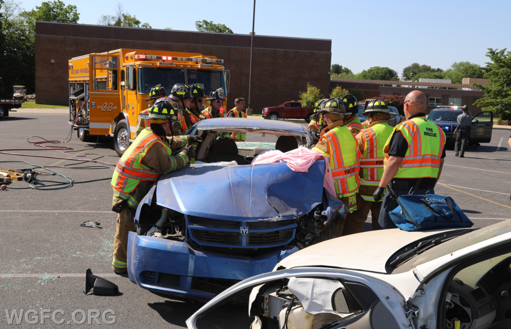 Firefighters and EMTs work to remove the roof on a damaged vehicle.