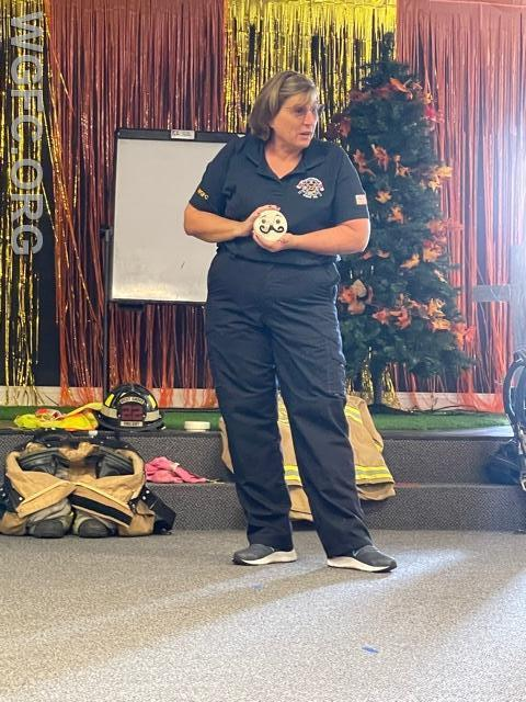 Firefighter Lisa shows off a smoke detector as part of the safety education session.
