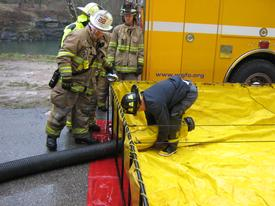 Henry sets up a standard hard sleeve hose through the drain of the tank.