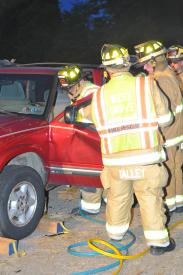Firefighters remove a vehicle door to gain access to a crash victim.
