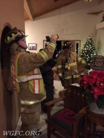 WGFC firefighters Joe Pearson and Bill Wohl explain to the homeowner the steps taken by the WGFC and how the wall temperature was being monitored using a thermal imaging camera.