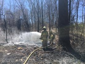 WGFC firefighters apply foam as a final step after battling a smoky brush and trash fire on State Road in New London.  Smoke could be seen as far away as West Grove and Landenberg.