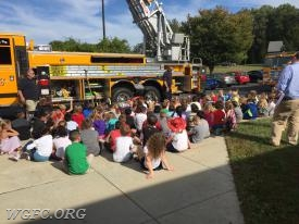 Lt Rob Kloss talking with students about fire fighting equipment carried on the fire trucks