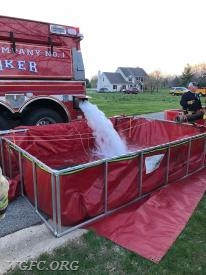 Water from Tanker 21 flows into one of two portable tanks to supply the fire scene operation. Each portable tank can hold 3000 gallons.