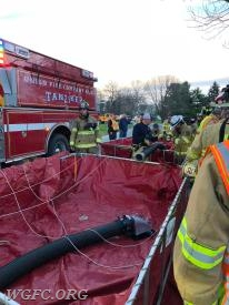 Here crews are setting up the twin portable tank operation.  The large suction line in the foreground is used to draft water from the combined tanks.   The second hose connects the portable thanks together.  With practice, both tanks and apparatus can be set up in minutes and be ready to accept 6000 gallons of water to supply a fire scene in nearly any location.