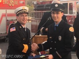 WGFC Past Chief and Current President Jeff SImpson handing the completion certificate to his son FF Tyler Simpson