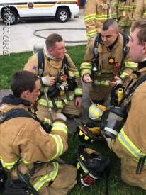 Crews discuss the training after coming out of the burn building.