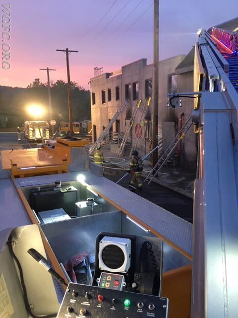 """This view from Ladder 22 shows the """"fire scene"""" with hose lines and ladders deployed as night falls."""