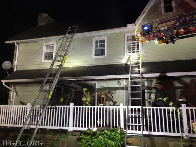 """Ladder 22 lights up the scene as crews open up a wall enveloped by fire on the structures """"B"""" side"""