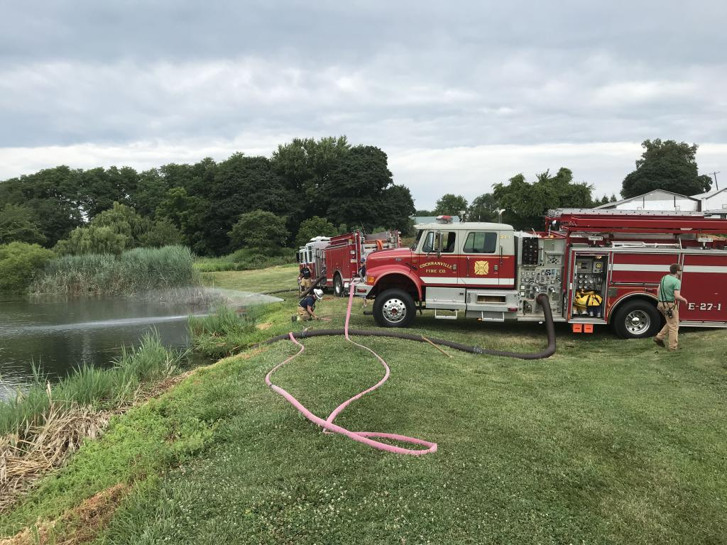 Pumpers from Oxford and Cochranville draft from the pond to supply tankers.
