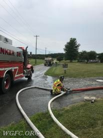 A water supply firefighter operates a supply valve to fill tankers in the shuttle.