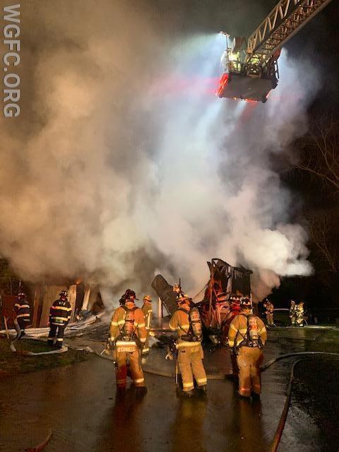 Crews prepare to pull apart the burning debris to extinguish the fire.