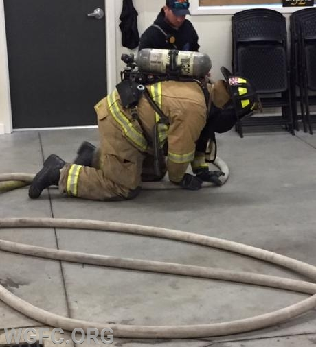 Firefighter using the coupling connection directional technique to find his way back to the truck.