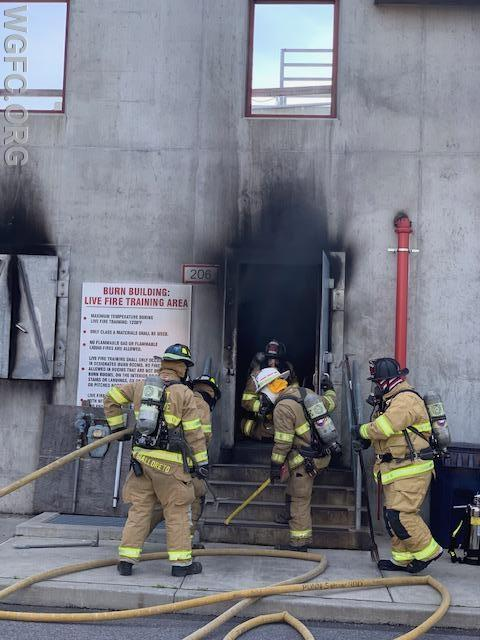 Crews from the West Grove Fire Company advance an attack line into a burning building as part of an all day training exercise at the County Fire School last week.