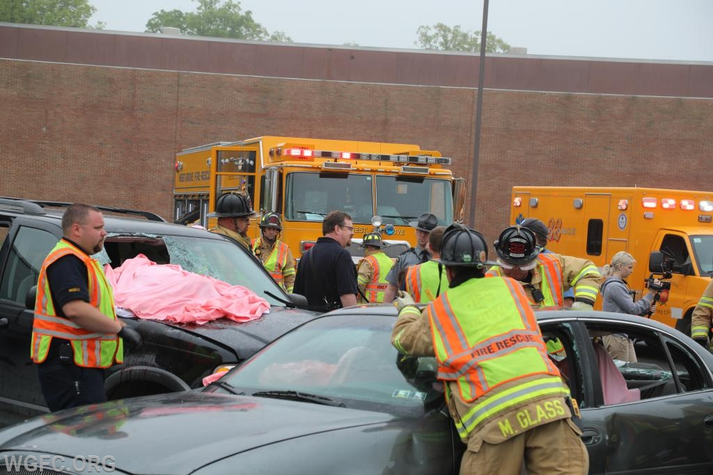 With an ambulance and rescue truck as background, EMS and fire personnel work on the damaged vehicles