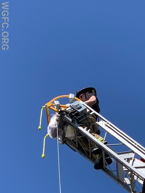 Firefighter Matt Glass at the top of Ladder 22 did the honors from about 75 feet above the parking lot.