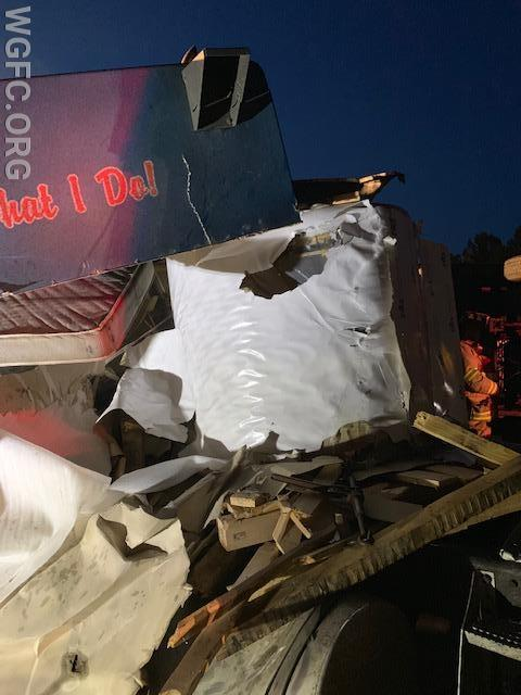 This photo shows the roll of aluminum sitting on the tractor, having crushed the truck cab