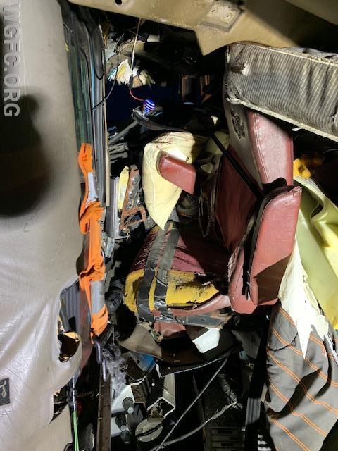 This close up shows the driver's seat, and how the cab was crushed around him.  His lower legs were entrapped and Engine 22-1's crew used hydraulic tools to move the seat back just enough to free his legs
