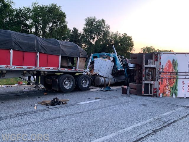 In this view, it can be seen how the second truck (at left), T-boned the first truck, which was on its side blocking the highway.  The large white area is the 9,500 pound roll of aluminum which pushed off the trailer and crushed the cab of the second truck
