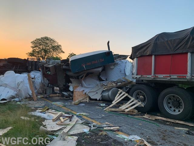 In the first morning light, the extent of the the damage and debris can be seen.  The cab of the second truck is at center -- three of the large aluminum rolls can be seen (in white)