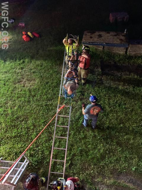 Patient being lowered from an elevated point using a ground ladder.