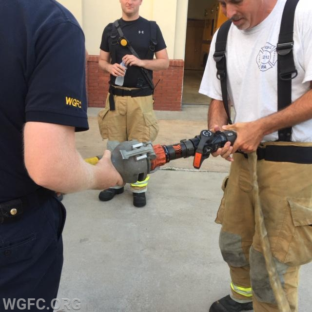 Members adding a foam expander device to a standard combination nozzle.