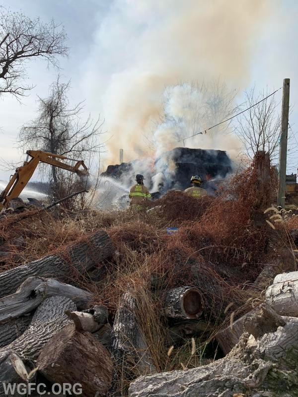 The pile of burning hay was adjacent to piles of cut up trees and debris.