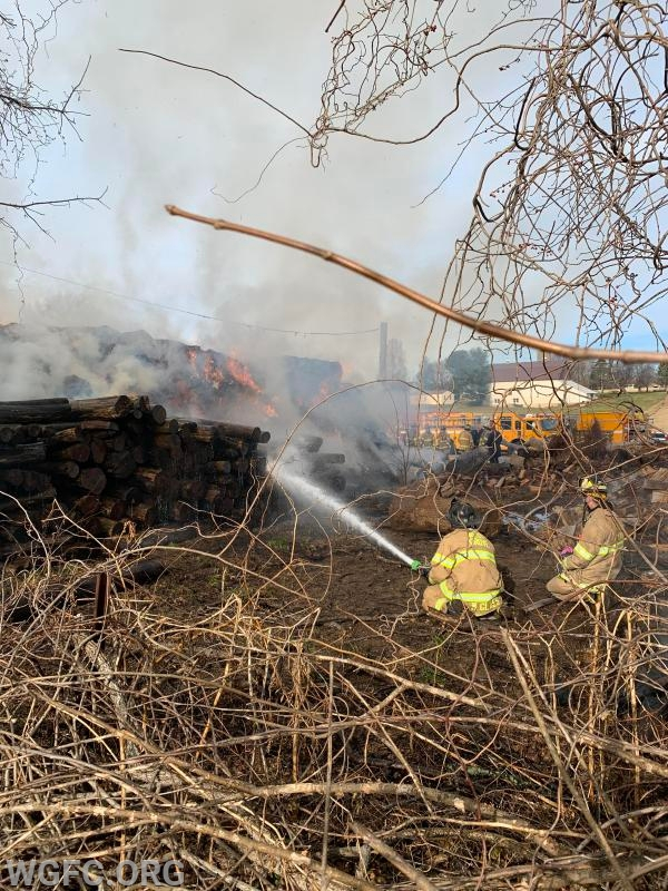 A hand line is deployed early in the fire to the rear of large hay bale pile.