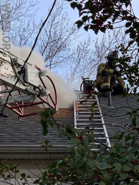 Ladder 21 crews work the roof -- this view shows smoke and heat venting from the attic area after a vent hole was cut
