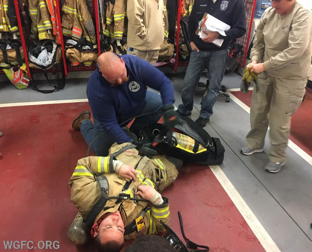 Members packaging a down firefighter while extending the air supply with a RIT pack.