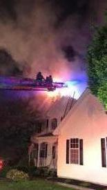 Ladder 22's crew ascends the aerial to vent the roof above the fire.