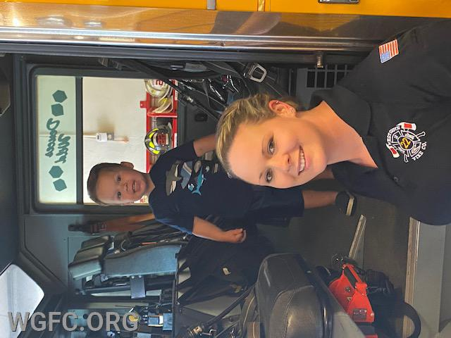 EMT Danielle Hughes led a large team that performed life-saving measures.  Here she is with Logan who is checking out WGFC's Engine 22-1.